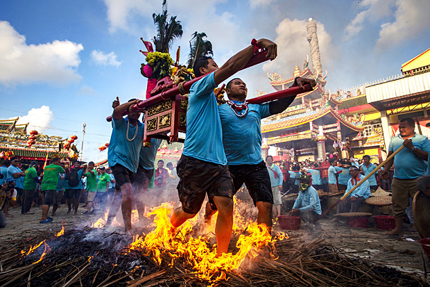 Dozens of followers join the fire-walking. Each bearer received a 'hu' or pha yan (a piece of talismanic cloth) from the Lim Ko Nieo Shrine before joining the celebration. They were soaked in nam mon (holy water) before the walk. The fire bed is made of burnt charcoal, covered by dry coconut leaves. While walking, some devotees scoop rice grains or salt and throw them into the fire, as a gesture to get rid of bad things. (Photo by Chayawat Manasiri)
