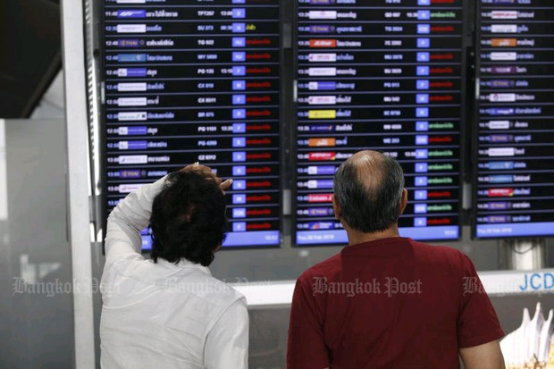 Passengers check a board at Suvarnabhumi airport after airlines cancelled flights to and from Europe Wednesday night. (Photo by Varuth Hirunyatheb)