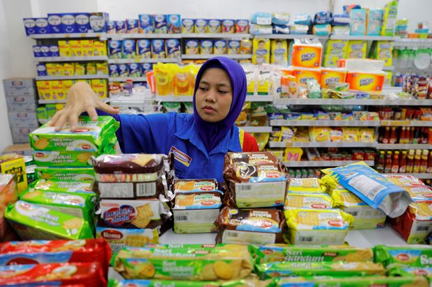 A shopkeeper arranges snacks to sell at a mini market in Jakarta on Feb 15. (Reuters photo)