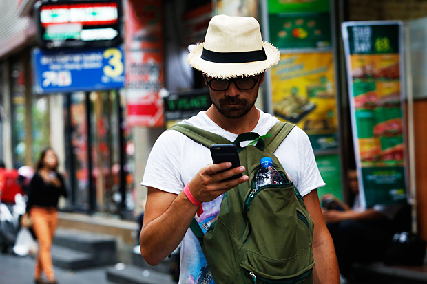 A foreign tourist looks at his phone while walking along Silom Road.  (Photo by Tanaphon Ongarttragoon)