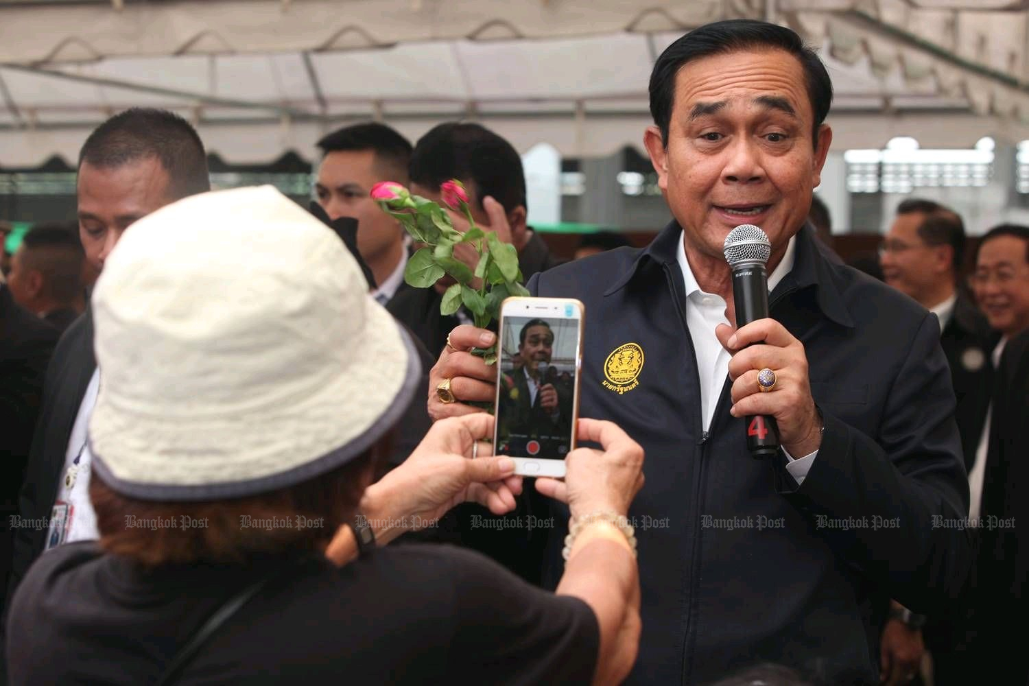 Prime Minister Prayut Chan-o-cha speaks and poses for a fan photo at the same time. He is expected to make his election campaign debut at Korat on Sunday. (Post Today photo)