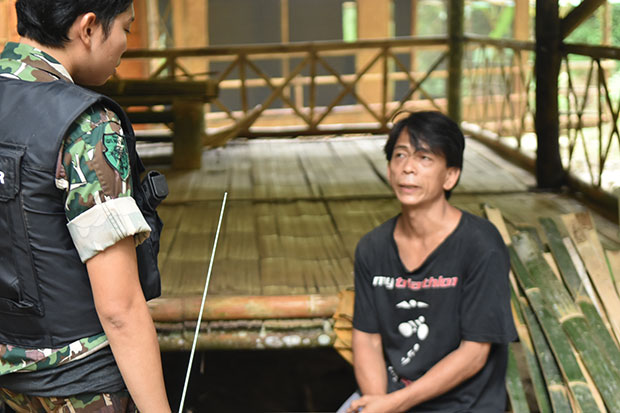 Karen man Tata, in black T-shirt, is arrested along with 12 others for poaching wildlife at Sai Yok National Park in Kanchanaburi on Oct 7 last year. On the left, assistant head of Sai Yok National Park Natenapha Ngamnate. (Photo by Piyarach Chongcharoen)