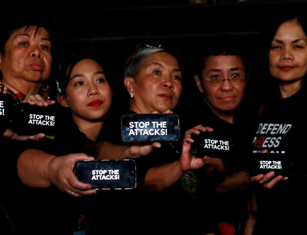 Journalists, including Rappler CEO Maria Ressa, raise their smartphones with displaying the words