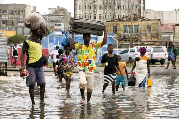 In this photo taken on Friday, and provided by the International Red Cross, people carry their personal effects after Tropical Cyclone Idai hit Beira, Mozambique. (Denis Onyodi/IFRC via AP)