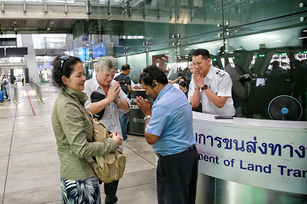 The Danish tourist and his Thai wife thank cabbie Somsri Larat (blue shirt) for the return of their bag containing 400,000 baht cash and personal documents on Monday. (Photo by Sutthiwit Chayutworakan)