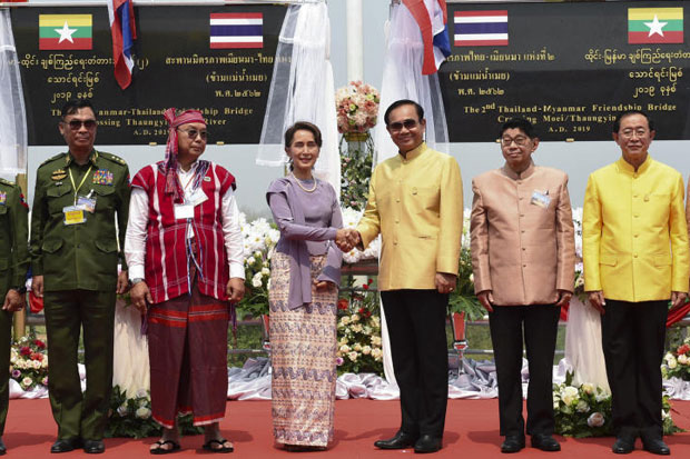 Prime Minister Prayut Chan-o-cha, third from right, shakes hands with Myanmar State Counsellor Aung San Suu Kyi during the opening ceremony for the second Thai-Myanmar friendship bridge across the Moei River, linking Mae Sot district in Tak province and Myawaddy in Myanmar, on Tuesday. (Government House photo)