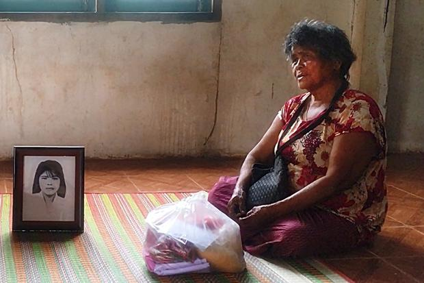 Jumsri Sikanya sits by a picture of her daughter Lamduan, at her home in Phen district, Udon Thani, on Wednesday. (Photo by Yuttapong Kamnodnae)