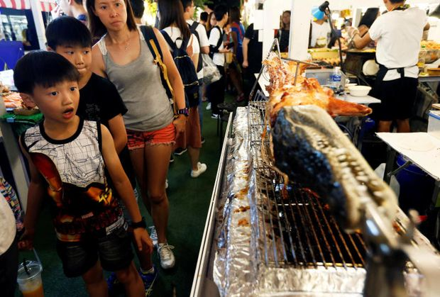 Tourist children react as they look at crocodile BBQ at a temporary night market to mark Chinese New Year in Bangkok on Feb 4, 2019. (Reuters file photo)