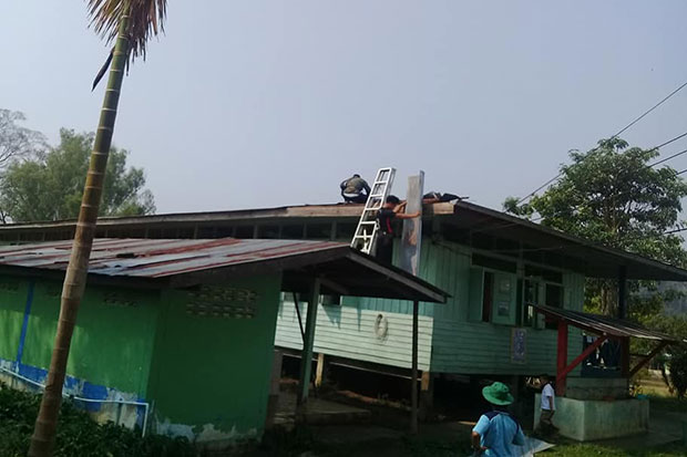 Workers at Ban Prophado School in Umphang district repair the roof of the school's 38-year-old wooden main building - again. (Photo taken from  Montri Jina Facebook page)