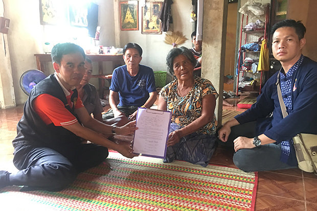 Jumsri Seekanya (second right) shows a document authorising Setthinari Venes, the Thai Women Network in the UK chairwoman, to handle all ceremonies for her daughter, Lamduan, at her house in Phen district on Thursday. (Photo by Yuttapong Kumnodnae)