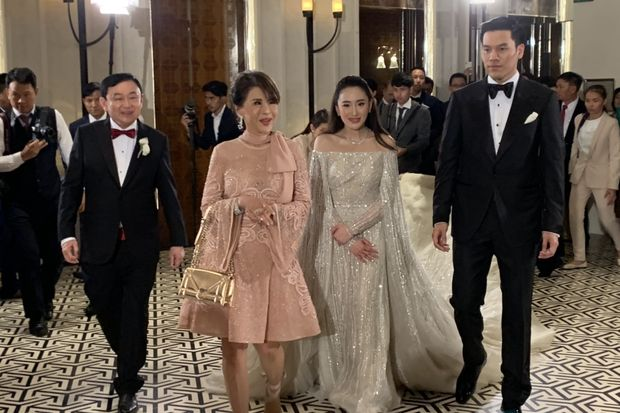 Princess Ubolratana (in pink dress) arrives at the wedding reception in Hong Kong. She was greeted by Thaksin Shinawatra (left) and the couple.