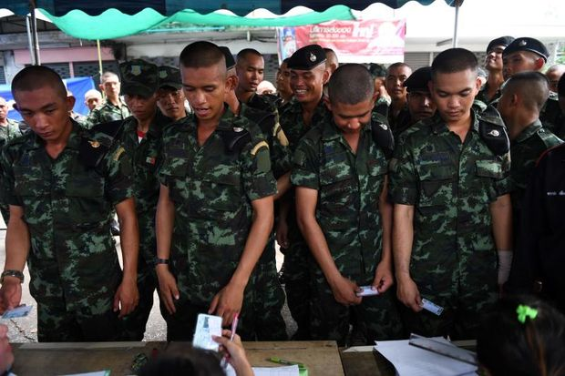 Royal Thai Army soldiers queue up to cast their ballots at a polling station in Bangkok on Sunday during Thailand's general election. (AFP photo)