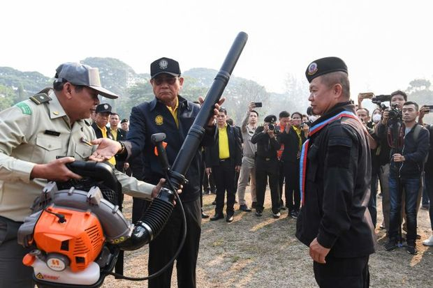 Bringing in the big guns: Thailand's Prime Minister Gen Prayut Chan-o-cha (centre) holds a leaf blower at an army base in Chiang Mai on Tuesday. (AFP photo)