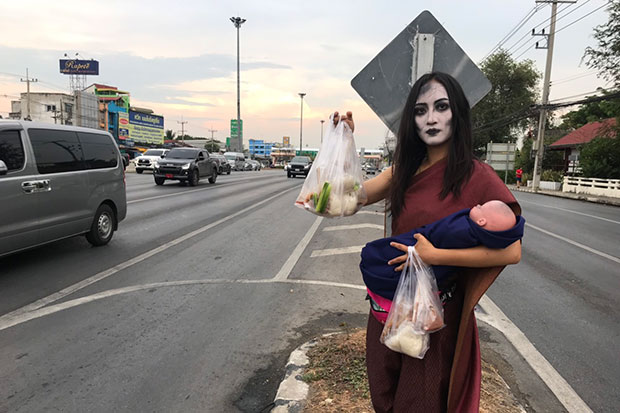 Erm, thought it was Songkran, not Halloween. Nannaphat Chalachainanpa, 23, dressed as the legendary ghost Mae Nak Phra Khanong, sells moo ping (grilled pork) with sticky rice at an intersection on Rotjana Road in Phra Nakhon Si Ayutthaya district of Ayutthaya on Sunday. (Photos by Sunthorn Pongpao)
