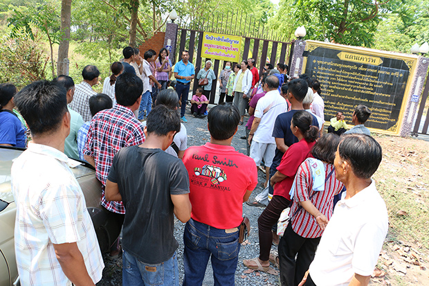 People stand in front of the closed gate to Vachiraphothiyan Monastery Temple in Pho Thale district of Phichit on Monday, where a sign reads that the temple is closed and will no longer give out drugs made from marijuana. (Photo by Sitthipoj Kebui)