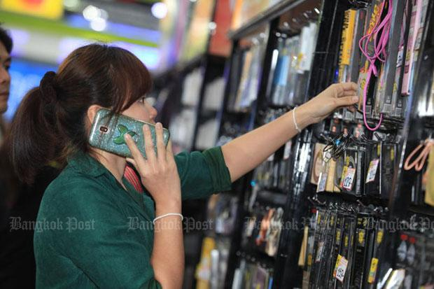 A woman checks out mobile phone accessories at a mobile phone fair in Bangkok in February. On Thursday Prime Minister Prayut Chan-o-cha, in his capacity as the chief of the National Council for Peace and Order, extends the licence fee payments for three major mobile phone operators. (File photo)
