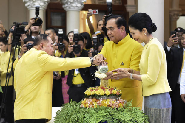 Deputy Prime Minister and Defence Minister Prawit Wongsuwon pours water on the hands of Prime Minister Prayut Chan-o-cha who presided over a 'Rod Nam Dam Hua' ceremony at Government House on Thursday. His wife Naraporn also attended the event. (Government House photo)