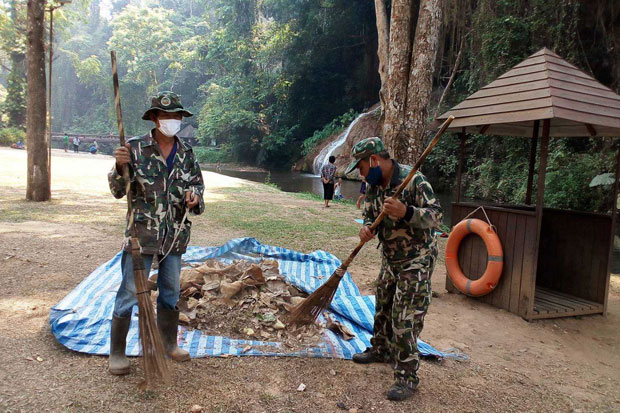 Park rangers collect dry leaves in a bid to stop a forest fire spreading in Phu Sang National Park in Phayao province on Thursday. (Photo by Sai-arun Pinaduang)