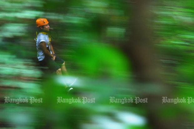 This file photo shows a tourist riding the Flight of the Gibbon zipline in Chiang Mai province. (Photo by Peerawat Jariyasombat)