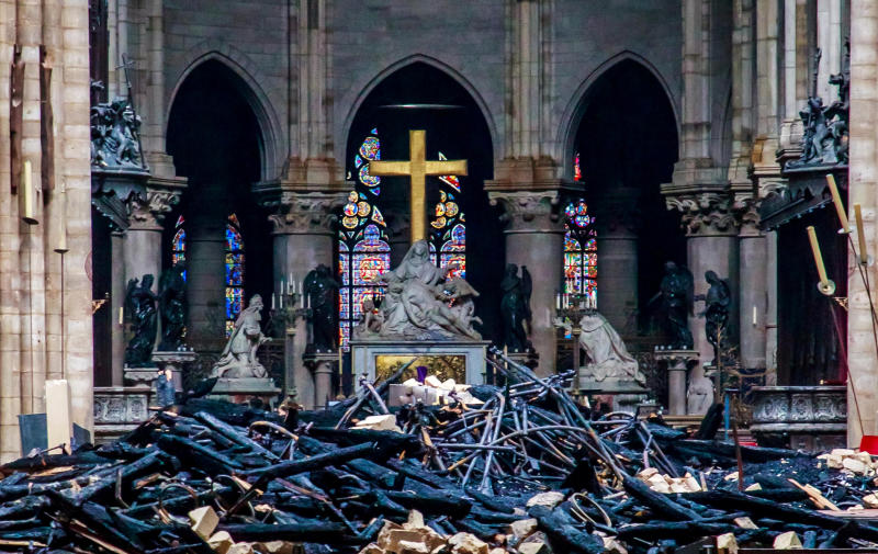 A view of the cross and sculpture of Pieta by Nicolas Coustou in the background of debris inside Notre-Dame in the aftermath of a fire that devastated the cathedral. (Reuters photo) Christophe Petit Tesson/Pool via REUTERS TPX IMAGES OF THE DAY
