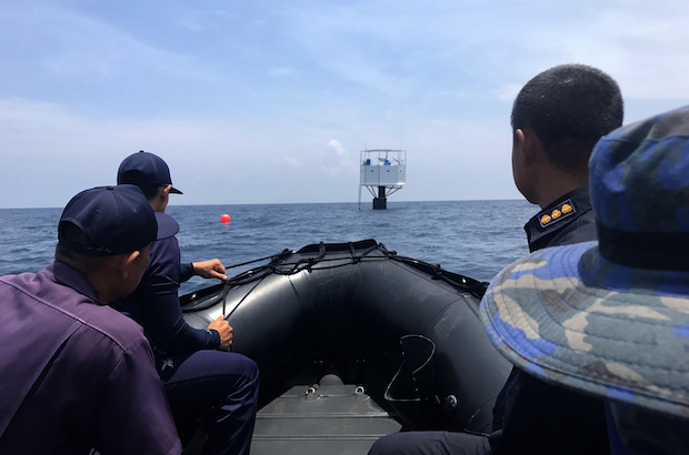 A navy team approaches the floating home formerly occupied by Chad Elwartowski and Supranee Thepdet off Phuket on Saturday. (Royal Thai Navy photo)