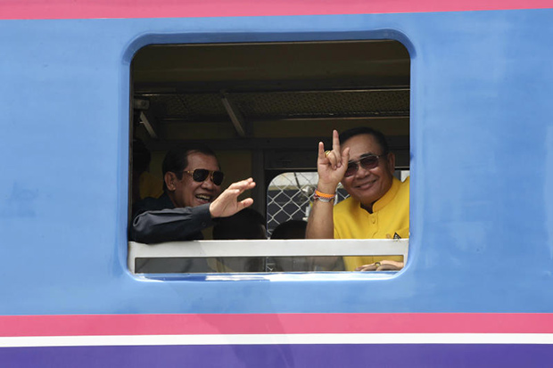 Cambodian Prime Minister Hun Sen (left) and Prime Minister Prayut Chan-o-cha wave from a window of the train before departing from Klong Luek station in Aranyaprathet district, Sa Kaeo, on Monday. (Photo: Cambodian government/AP)