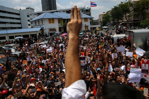 Thanathorn Juangroongruangkit, leader of the Future Forward Party, and his supporters flash three-finger salutes as he leaves a police station after hearing a sedition complaint filed by the army in Bangkok on April 6. (Reuters photo)