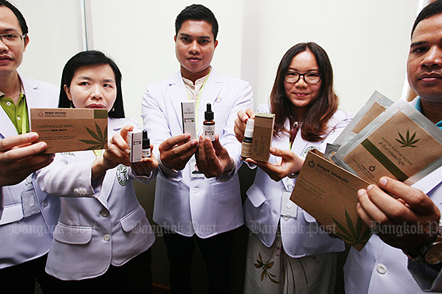 Rangsit University researchers and pharmacists show off some of the different types of medicine derived from cannabis during a press briefing on Tuesday announcing the opening of its medicinal cannabis research institute. (Photo by Apichit Jinakul)
