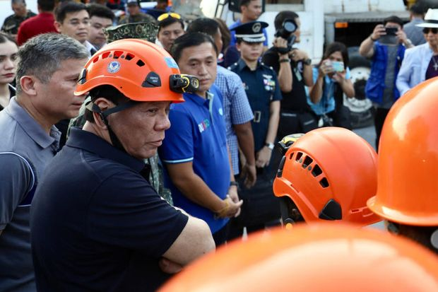 Philippine President Rodrigo Duterte, bottom left, talks to rescuers as he visits an earthquake-damaged building where operations continue for trapped people in Porac town, Pampanga province, northern Philippines on Tuesday.  (Richard Madelo/Malacanang Presidential Photographers Division via AP)