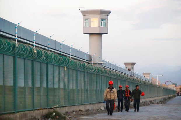 FILE PHOTO: Workers walk by the perimeter fence of what is officially known as a vocational skills education centre in Dabancheng in Xinjiang Uighur Autonomous Region, China Sept 4, 2018. (Reuters)