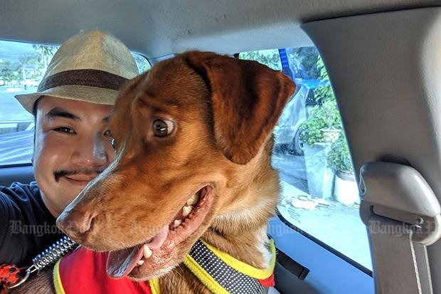 Vitisak Payalaw sits behind Boonrod, the dog he helped rescue from the ocean, as he prepares to take him from a shelter in Hat Yai district, Songkhla, to his home in Khon Kaen on Saturday. (Photo from Boonrod Facebook account)