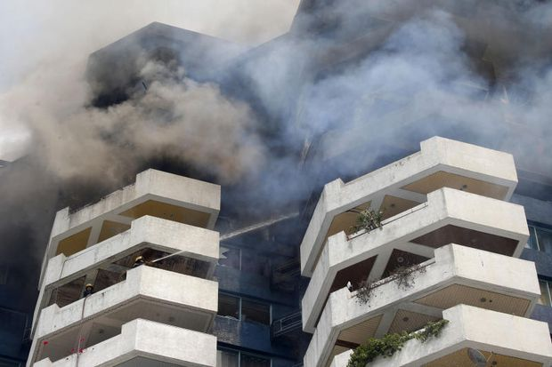 Firefighters train their hoses on a fire consuming the top floors of the 21-storey Pacific Coastal Plaza condominium on Monday, in Manila, Philippines. (AP photo)