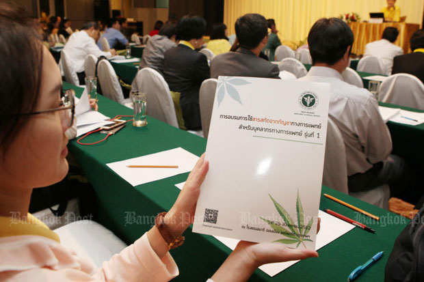 An attendee at the course on the medical use of marijuana on Monday shows the folder  handed out by the Department of Medical Services. (Photo by Apichit Jinakul)