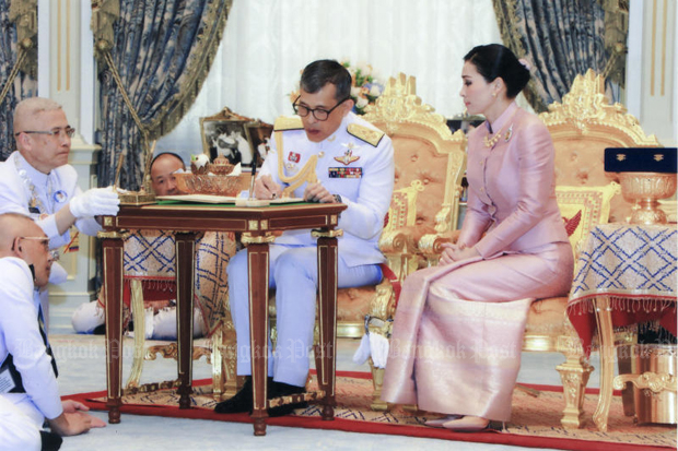 His Majesty the King signs marriage registration documents while Queen Suthida looks on during a ceremony at the Dusit Palace on Wednesday. (Royal Household Bureau photo)