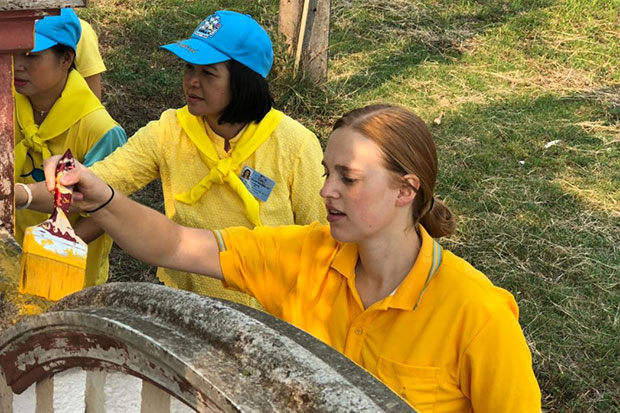 American volunteer Caitlin Navratil joins local residents and municipal officials in tambon Ngim of Pong district in Phayao to paint the walls at the Chalermprakiart health park to mark His Majesty the King's coronation. (Photo by Saiarun Pinaduang)