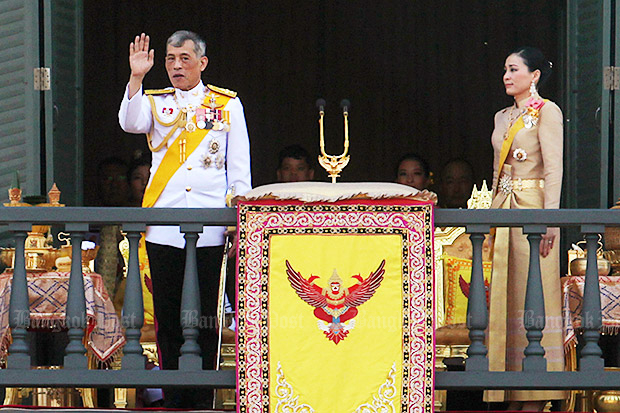 Their Majesties the King and the Queen greet an audience from the balcony of the Suddhaisavarya Prasad Hall in the Grand Palace on Monday. (Photo by Wichan Charoenkiatpakul)