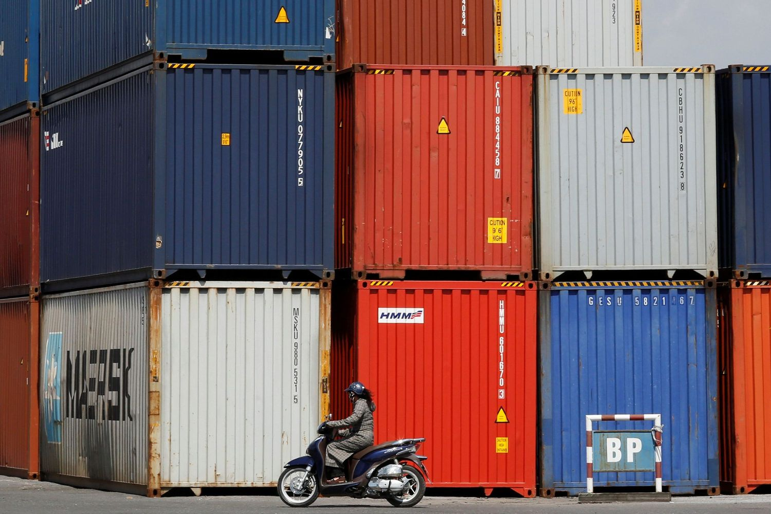 A woman rides a motorcycle as she passes containers at Hai Phong port, Vietnam, on Sept 25 last year. (Reuters photo)