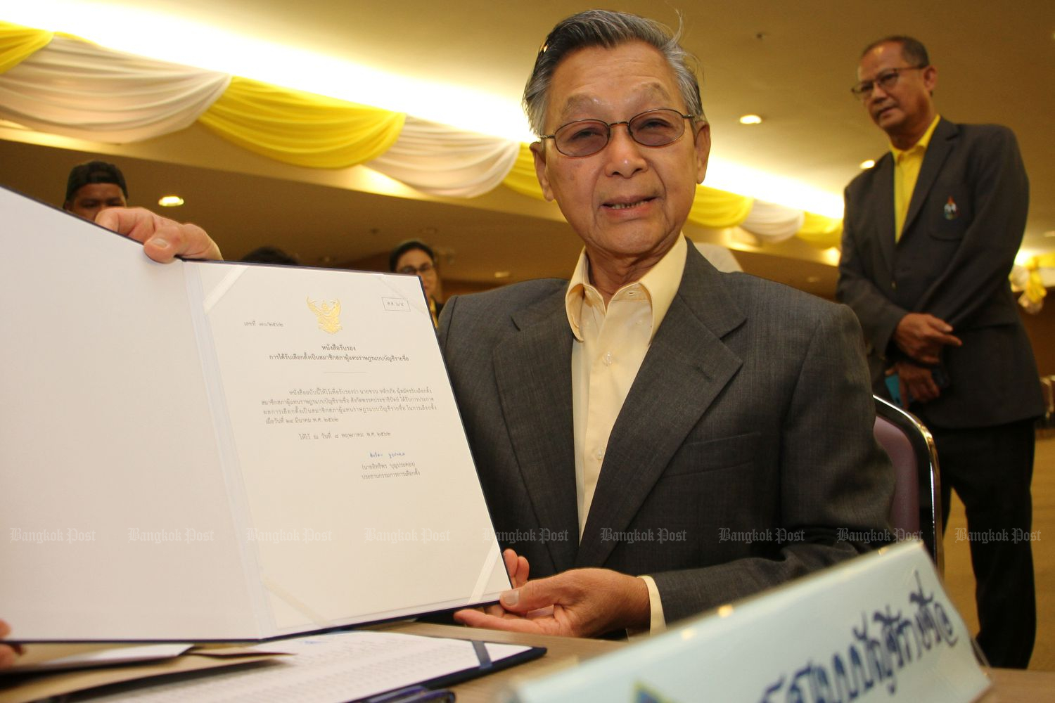 Former prime minister Chuan Leekpai shows a letter of endorsement from the Election Commmission at the EC office in Bangkok on Friday. (Photo by Tawatchai Kemgumnerd)