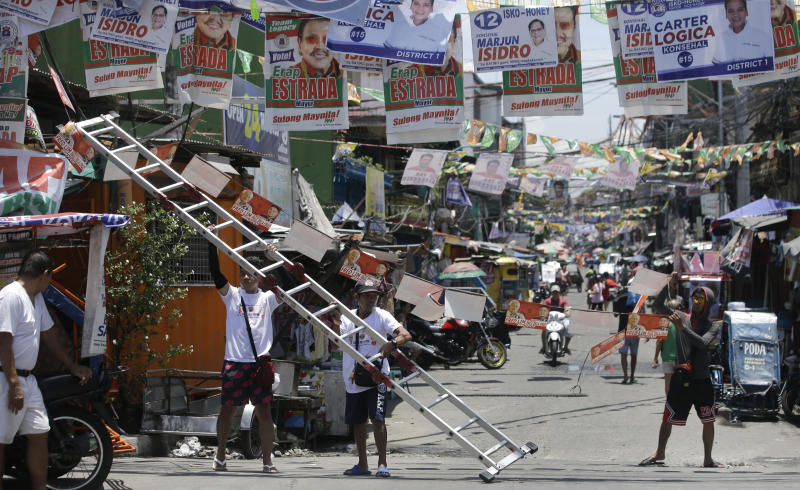 Workers place election campaign posters along a street at the slum district of Tondo, Manila, Philippines on May 9. (AP photo)