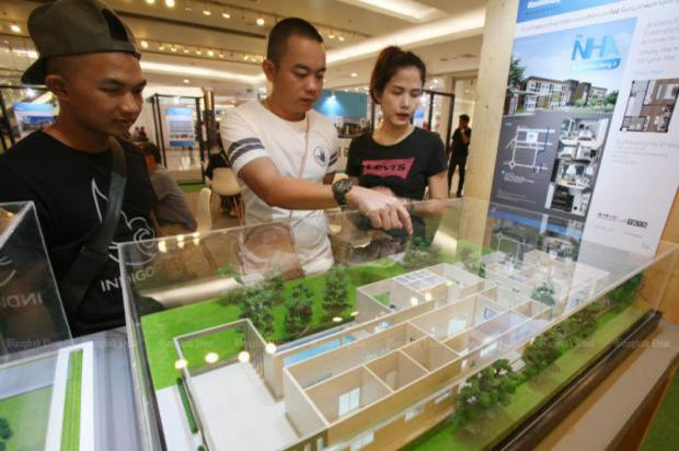 People browse housing models offered by the National Housing Authority. The NHA's low-priced housing projects will get a boost from the recently approved tax perks. (Photo by Apichit Jinakul)
