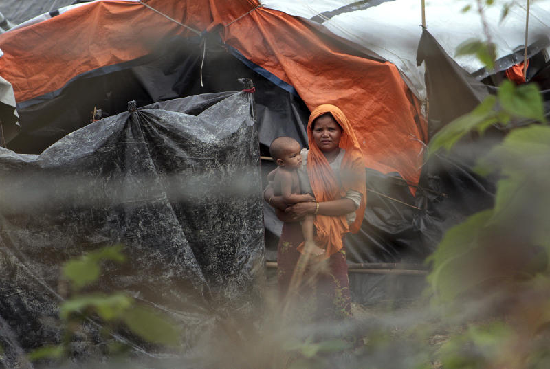 In this June 29, 2018, file photo, Rohingya refugees look out from their camp near a fence during a government-organised media tour to a no-man's land between Myanmar and Bangladesh, near Taungpyolatyar village, Maung Daw, northern Rakhine State, Myanmar. (AP)