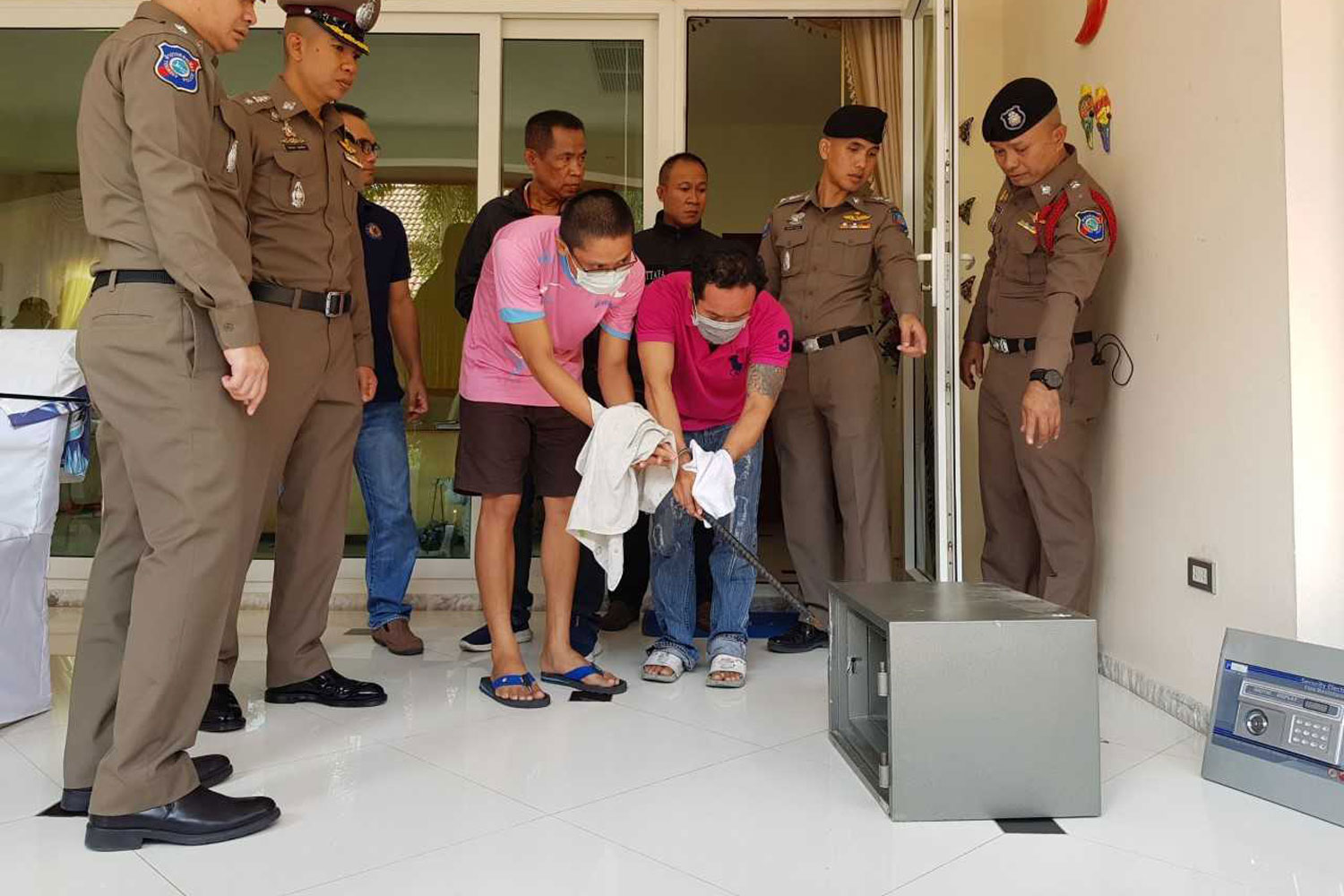 Police have the two suspected burglars re-enact their crime at the house of an Irishman in Pattaya City on Wednesday. (Photo by Chaiyot Pupattanapong)