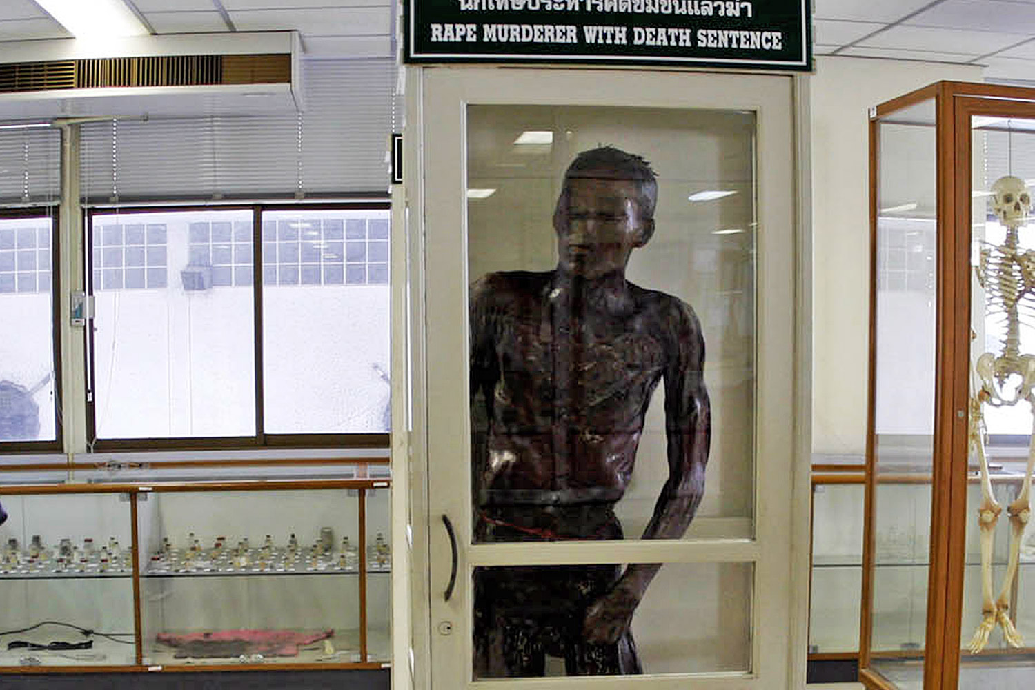 Visitors look at exhibits at Siriraj Hospital museum, including the cadaver of the notorious serial killer Si Quey, right. Pattarachai Preechapanich
