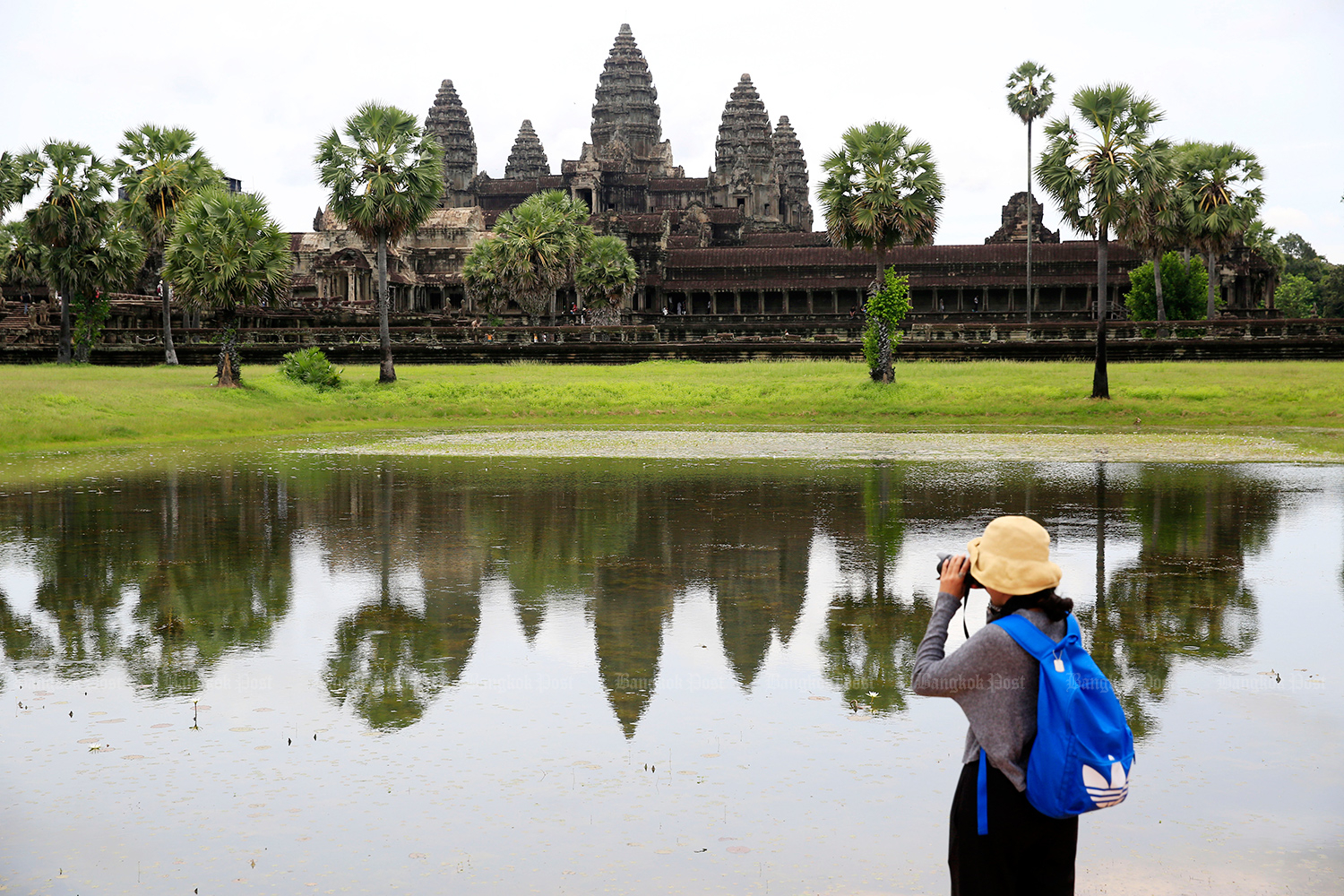 A tourist takes pictures of Angkor Wat in Siem Reap. (Post Today photo)