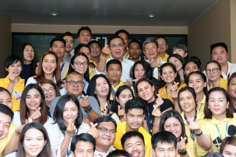 Prime Minister Prayut Chan-o-cha poses for pictures with Government House reporters on May 17 when he shared the last meal with them in the lead-up to the formation of the next government. (Photo by Chanat Katanyu)