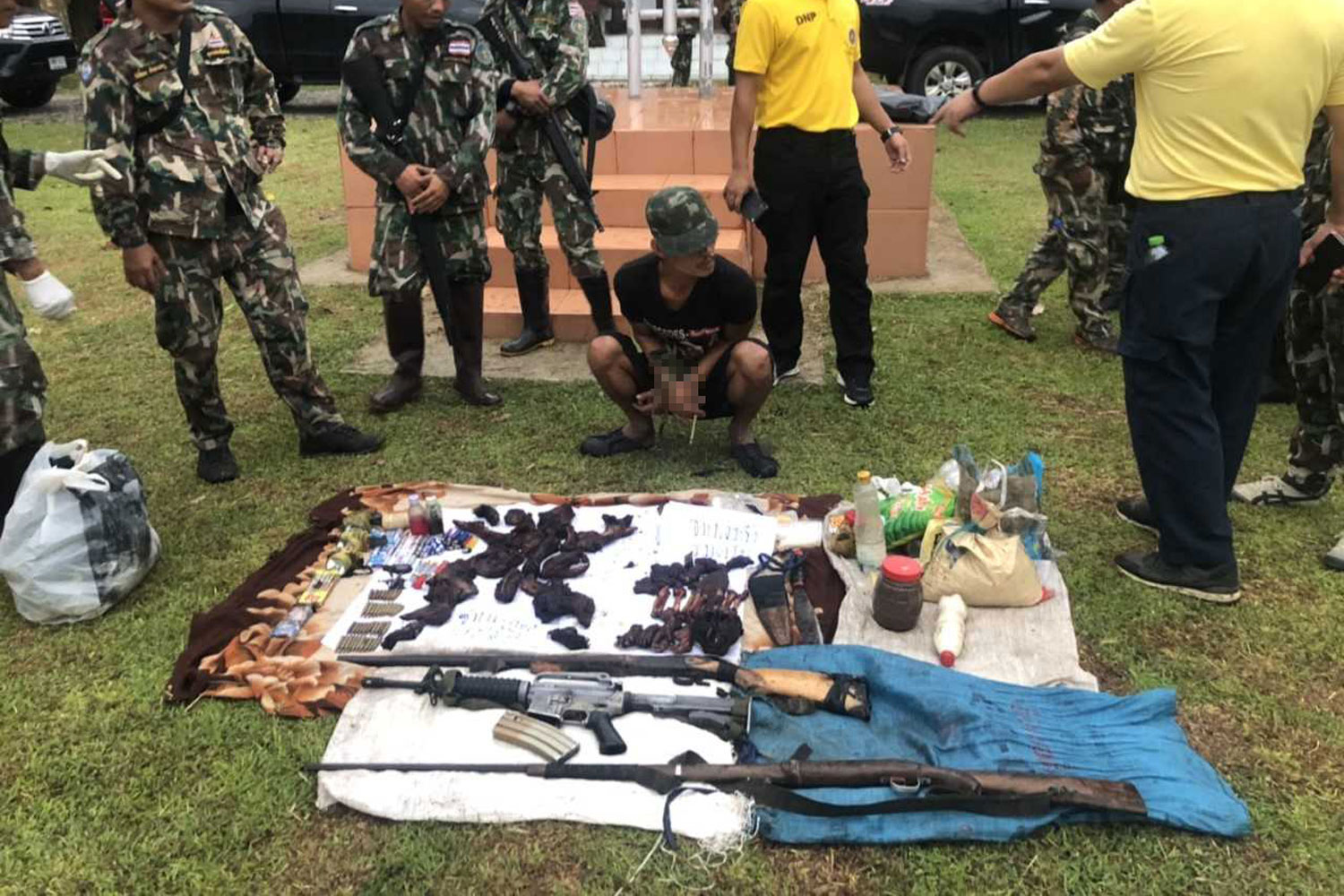 Karen hunter Satu, 26, is brought to the office of the Sai Yok National Park in Kanchanaburi province after he was arrested with the bearcat and macaque carcasses and the weapons in the national park on Wednesday. (Photo from the Sai Yok National Park office)