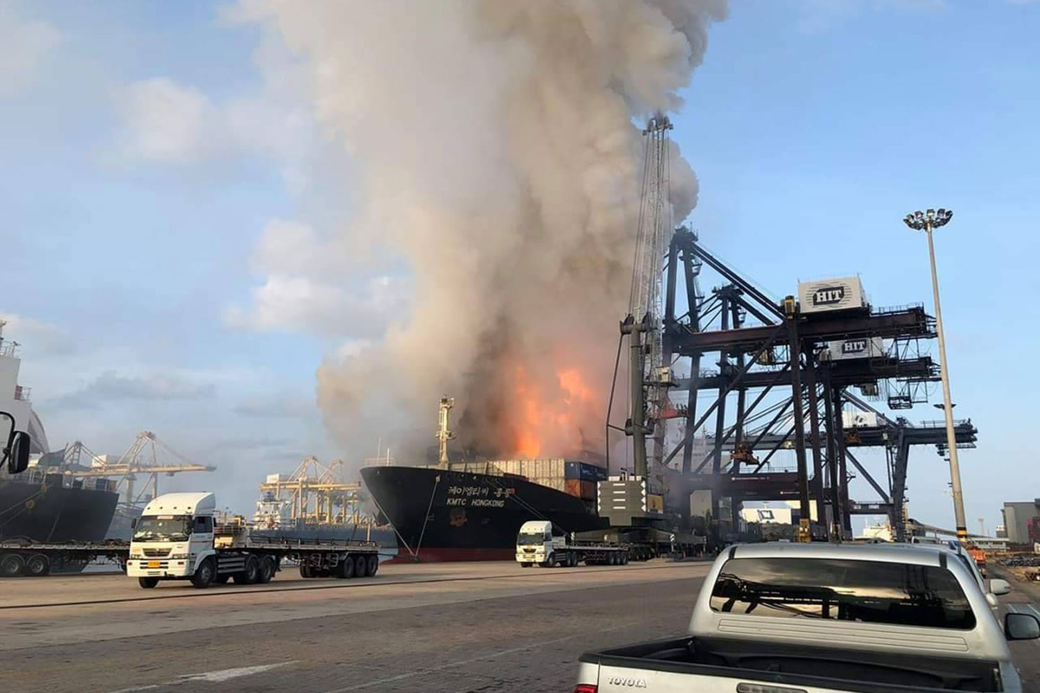 Thick black smoke billows from a cargo ship at Laem Chabang port in Sri Racha at dawn on Saturday. At least 50 people, mostly crew members working in the area, developed skin and eye trouble and were treated at hospital. (Photo by Trinai Jansrichol)