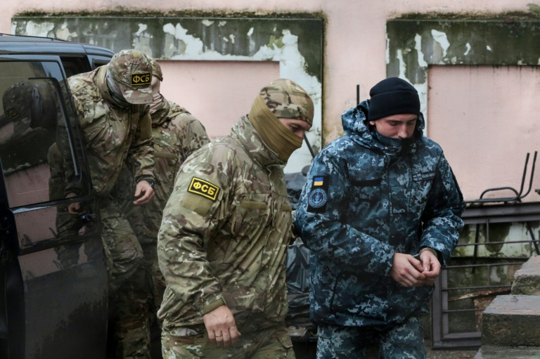 A Russian FSB security service officer escorts a detained Ukrainian sailor in Crimea in November -- a total of 24 sailors are still being held by Russia along with three naval vessels from Ukraine