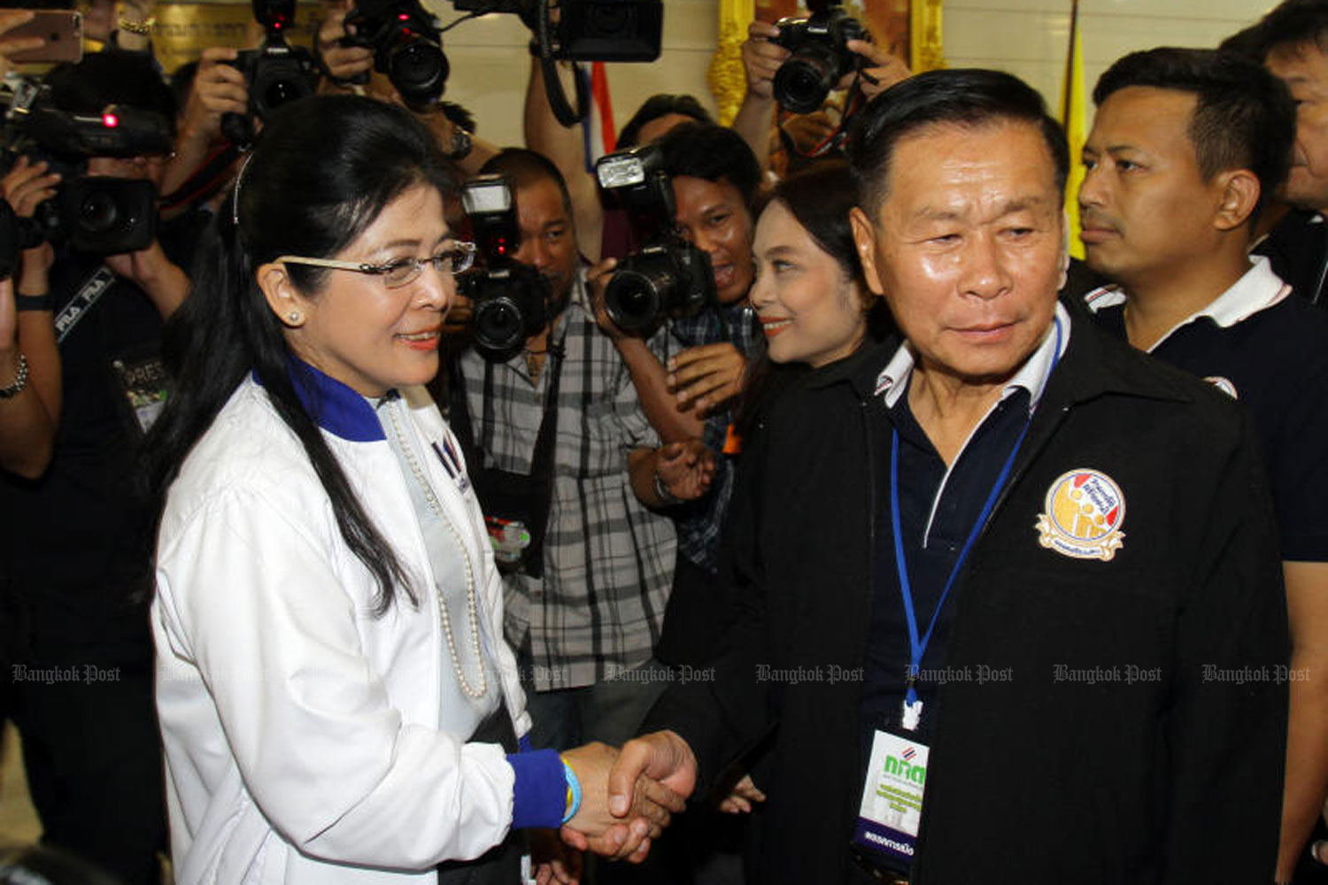 Seriruamthai Party leader Pol Gen Sereepisuth Temeeyaves, right, shakes hand with Pheu Thai key figure Khunying Sudarat Keyuraphan when they registered as party list candidates at the government complex in Bangkok in February. (Photo by Tawatchai Kemgumnerd)