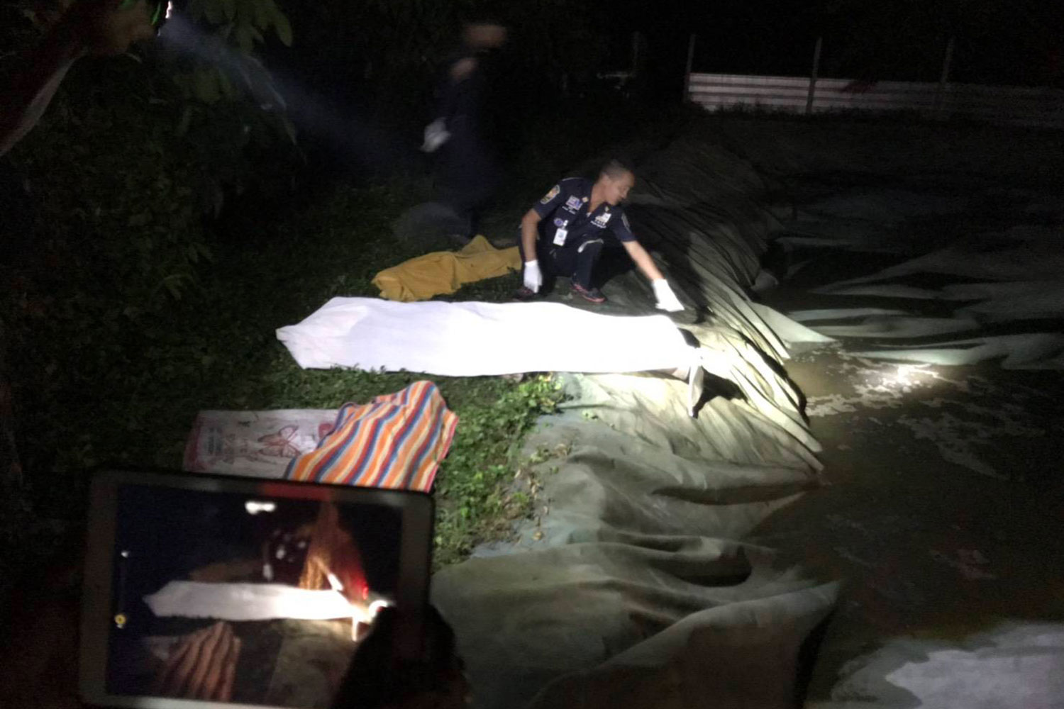 Three bodies of a pig farm owner and his two daughters age 7, and 9 are retrieved from the farm's waste treatment pond in Tamot district, Phatthalung province, on Wednesday night. (Photo supplied by Tamot district office via Assawin Pakkawan)